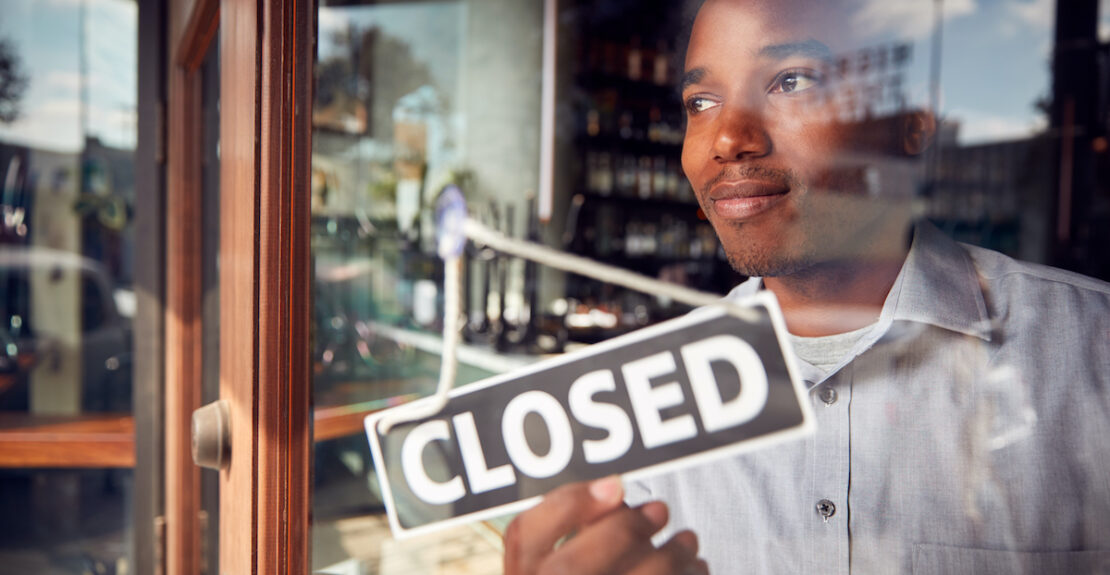 Male Owner Of Coffee Shop Or Restaurant Turning Round Closed Sign On Door Of Failed Business